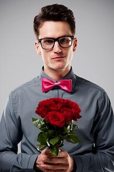 Uśmiechnięty mężczyzna trzyma czerwone róże