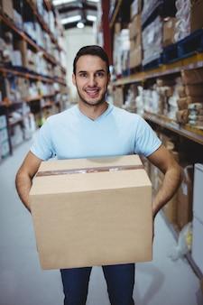 Uśmiechnięty mężczyzna trzyma dużego pudełko w magazynie