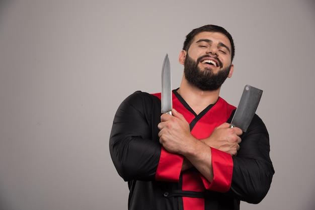 Uśmiechnięty mężczyzna trzyma dwa noże na ciemnej ścianie.