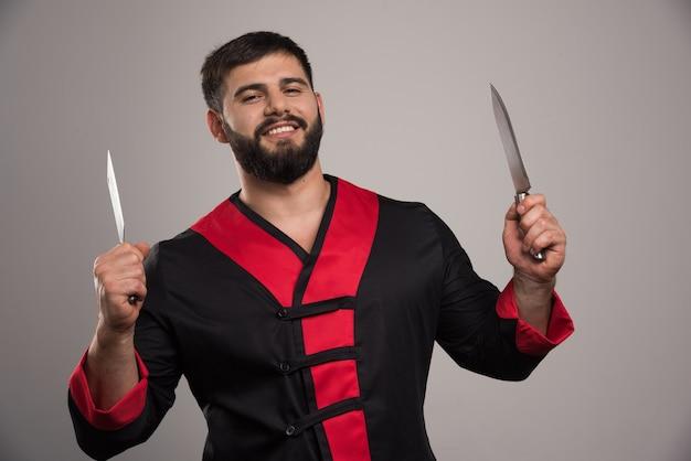 Uśmiechnięty mężczyzna trzyma dwa noże na szarej ścianie