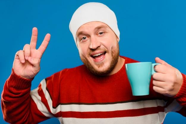 Uśmiechnięty mężczyzna trzyma filiżankę kawy