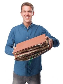 Uśmiechnięty mężczyzna trzyma kilka folderów roboczych