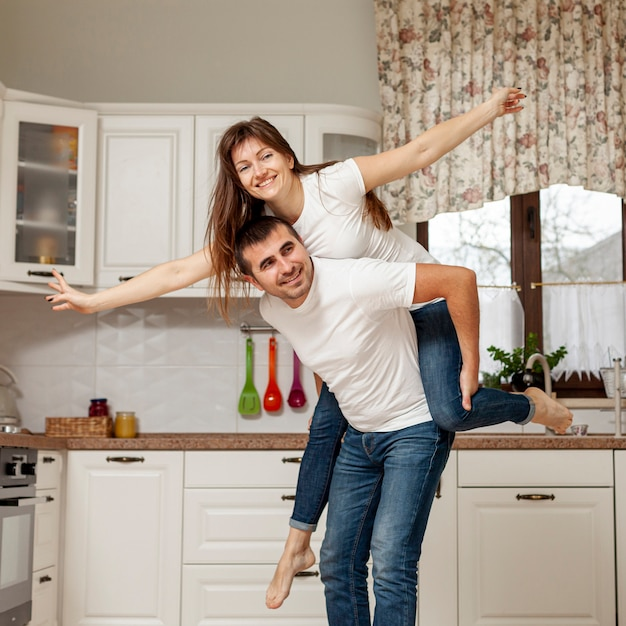 Uśmiechnięty mężczyzna trzyma kobietę na plecach