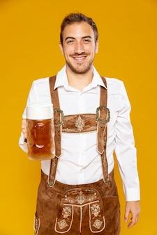 Uśmiechnięty mężczyzna trzyma kufel piwa
