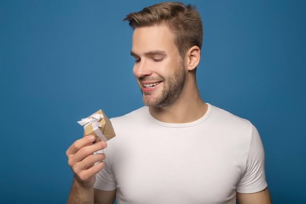 Uśmiechnięty mężczyzna trzyma małego prezent odizolowywający na błękicie