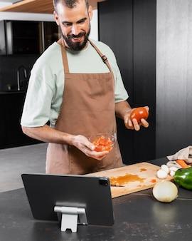 Uśmiechnięty mężczyzna trzyma pomidora