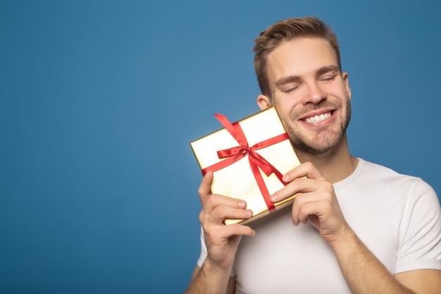 Uśmiechnięty mężczyzna trzyma prezent odizolowywający na błękicie z zamkniętymi oczami