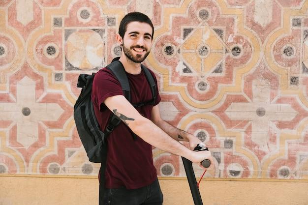 Uśmiechnięty mężczyzna trzyma rękojeści e-hulajnoga