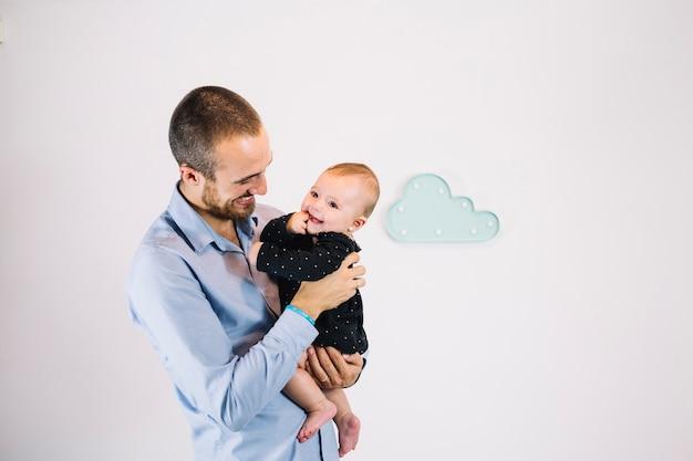 Uśmiechnięty mężczyzna trzyma rozochoconego dziecka