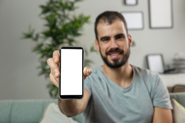 Uśmiechnięty mężczyzna trzyma smartfon w domu