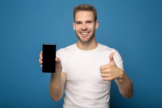 Uśmiechnięty mężczyzna trzyma smartphone i pokazuje kciuk up odizolowywającego na błękicie