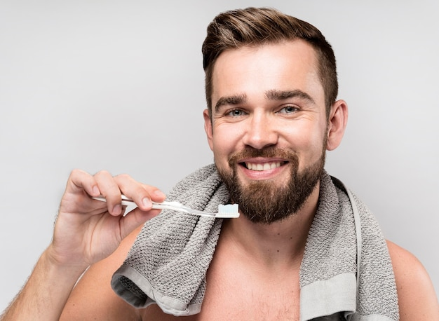 Uśmiechnięty mężczyzna trzyma szczoteczkę do zębów