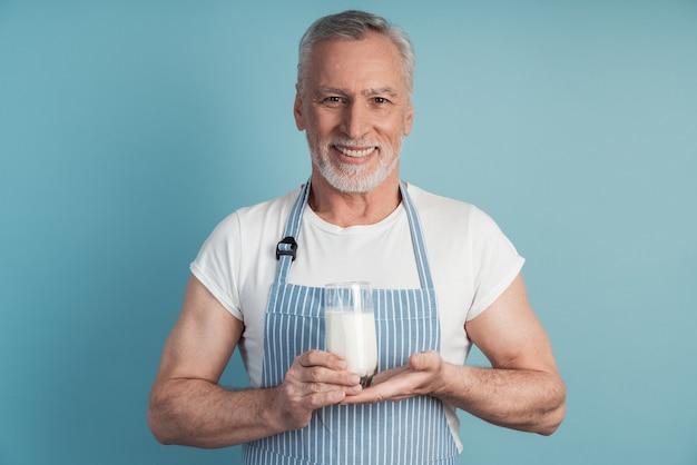 Uśmiechnięty mężczyzna trzyma szklankę mleka