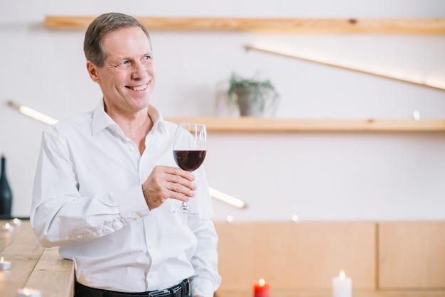Uśmiechnięty mężczyzna trzyma szkło wino