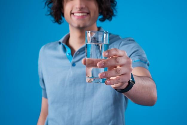 Uśmiechnięty mężczyzna trzyma szkło woda w jego ręce