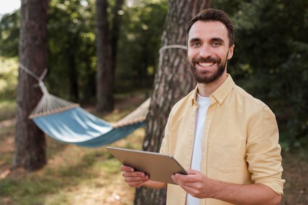 Uśmiechnięty mężczyzna trzyma tablet podczas kempingu na świeżym powietrzu