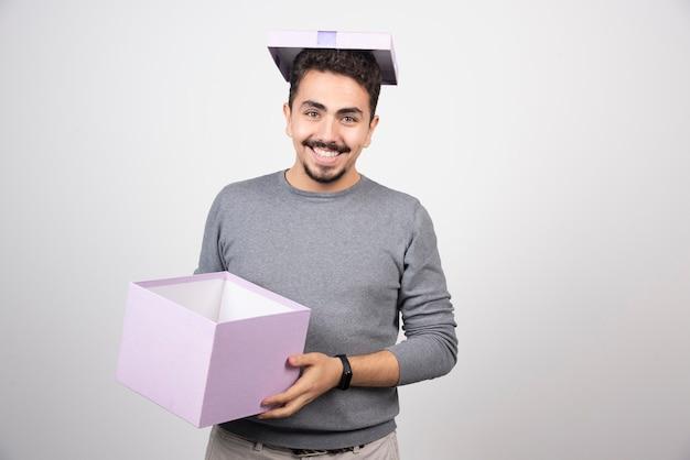 Uśmiechnięty mężczyzna trzyma w rękach fioletowe pudełko.