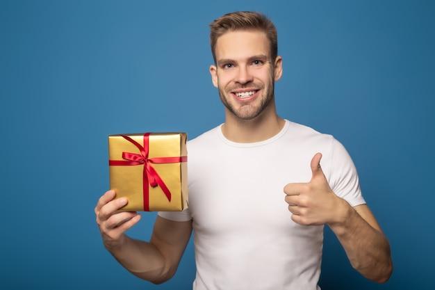 Uśmiechnięty mężczyzna trzyma złotego prezent i pokazuje kciuk up odizolowywającego na błękicie