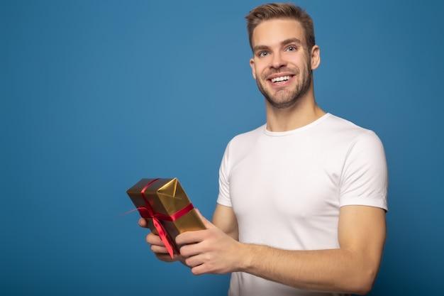 Uśmiechnięty mężczyzna trzyma złotego prezent odizolowywający na błękicie