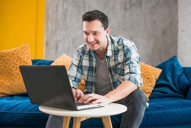 Uśmiechnięty mężczyzna używa laptop w domu