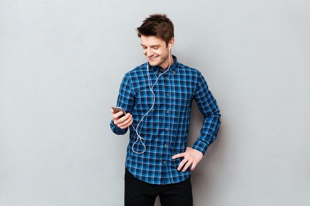 Uśmiechnięty mężczyzna używa smartphone wybierać muzykę
