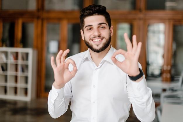 Uśmiechnięty mężczyzna w białej koszula pokazuje ok gest w biurze