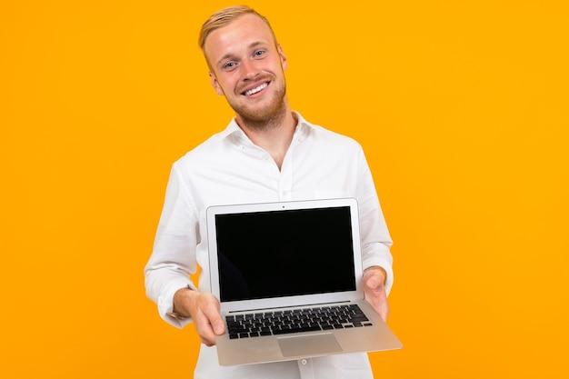 Uśmiechnięty mężczyzna w białej koszuli pokazuje ekran laptopa z makiety