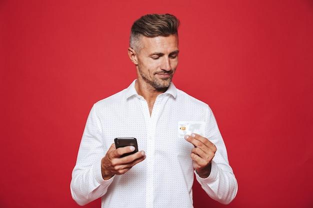 Uśmiechnięty mężczyzna w białej koszuli trzymający kartę kredytową i smartfona na czerwonym tle