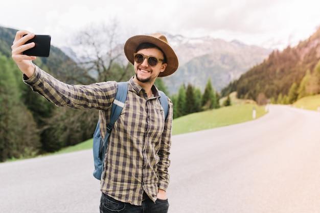 Uśmiechnięty mężczyzna w brązowym kapeluszu stojący z ręką w kieszeni i robienie selfie podczas łapania samochodu na drodze