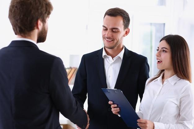 Uśmiechnięty mężczyzna w garniturze uścisk dłoni jako cześć w biurze