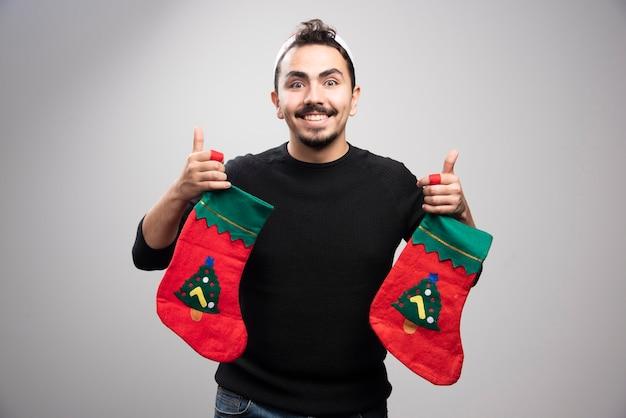 Uśmiechnięty mężczyzna w kapeluszu świętego mikołaja, trzymając skarpety świąteczne.