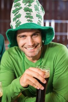 Uśmiechnięty mężczyzna w kapeluszu toast piwo