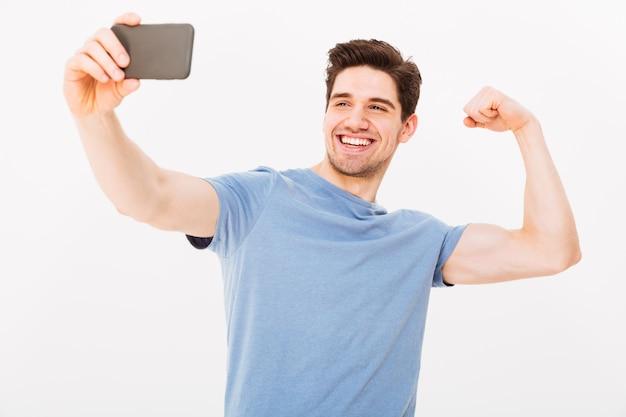 Uśmiechnięty mężczyzna w koszulce robi selfie na smartphone podczas gdy pokazywać jego biceps nad szarości ścianą
