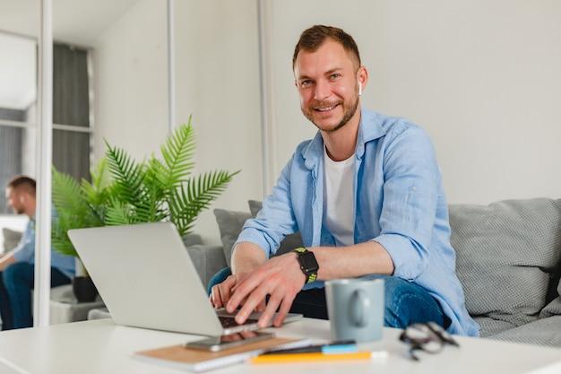 Uśmiechnięty mężczyzna w koszuli siedzi zrelaksowany na kanapie w domu przy stole, pracując online na laptopie z domu