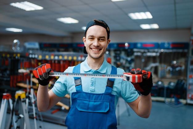 Uśmiechnięty mężczyzna w mundurze trzyma taśmę pomiarową w sklepie z narzędziami tool