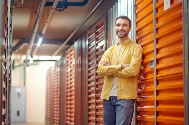Uśmiechnięty mężczyzna w pobliżu drzwi garażowych w piwnicy