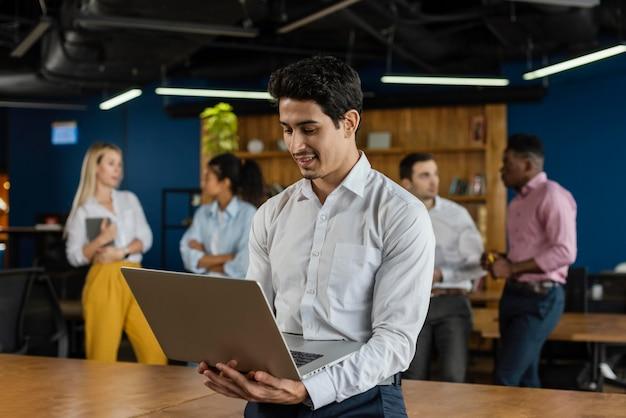 Uśmiechnięty mężczyzna w pracy trzymając laptopa