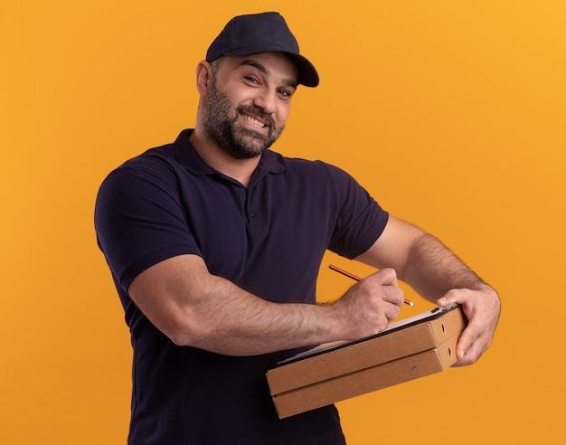 Uśmiechnięty mężczyzna w średnim wieku dostawy w mundurze i czapce pisze coś w schowku na pudełkach po pizzy na białym tle na żółtej ścianie