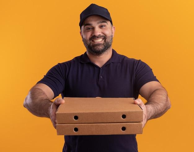 Uśmiechnięty mężczyzna w średnim wieku dostawy w mundurze i czapce trzyma pudełka po pizzy z przodu na białym tle na żółtej ścianie