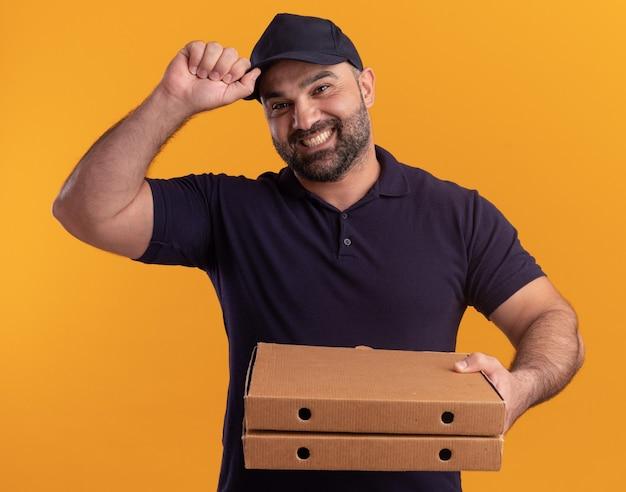 Uśmiechnięty mężczyzna w średnim wieku dostawy w mundurze i czapce, trzymając pudełka po pizzy i trzymając czapkę na białym tle na żółtej ścianie