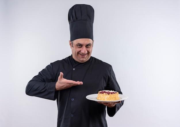 Uśmiechnięty mężczyzna w średnim wieku kucharz w mundurze szefa kuchni pokazuje ciasto na talerzu w ręku z miejsca na kopię