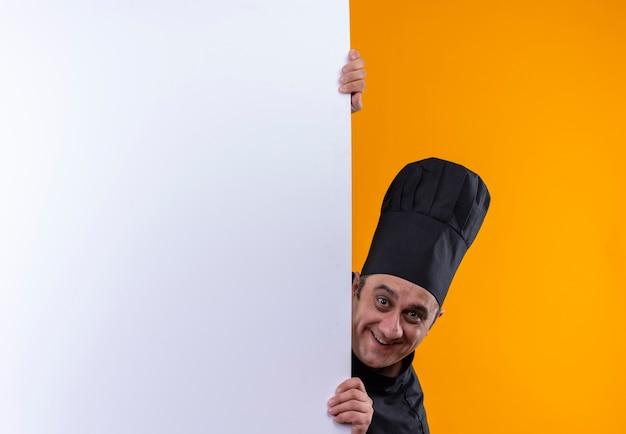 Uśmiechnięty mężczyzna w średnim wieku kucharz w mundurze szefa kuchni trzymając białą ścianę na żółtym tle z miejsca na kopię