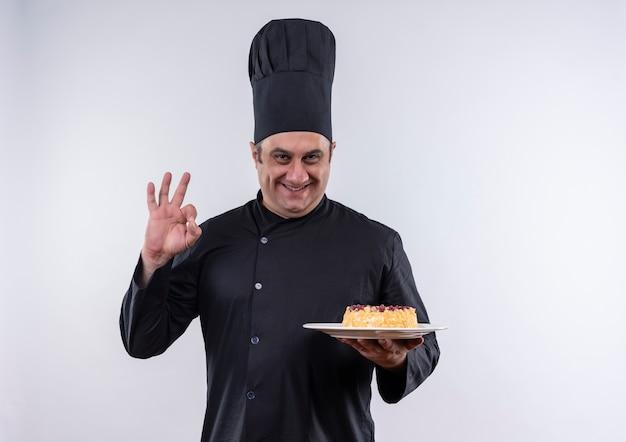 Uśmiechnięty mężczyzna w średnim wieku kucharz w mundurze szefa kuchni trzymając ciasto na talerzu z miejsca na kopię