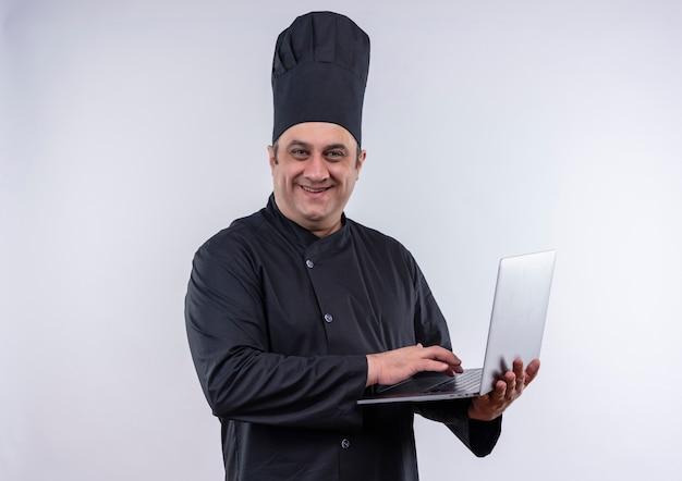 Uśmiechnięty mężczyzna w średnim wieku kucharz w mundurze szefa kuchni używał laptopa w ręku