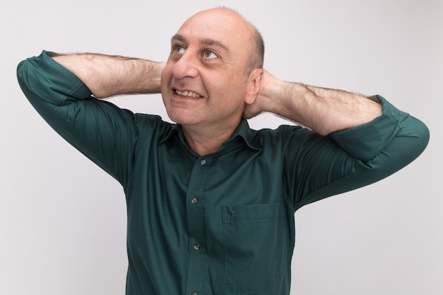 Uśmiechnięty mężczyzna w średnim wieku na sobie zieloną koszulkę kładąc rękę na głowę na białym tle na białej ścianie