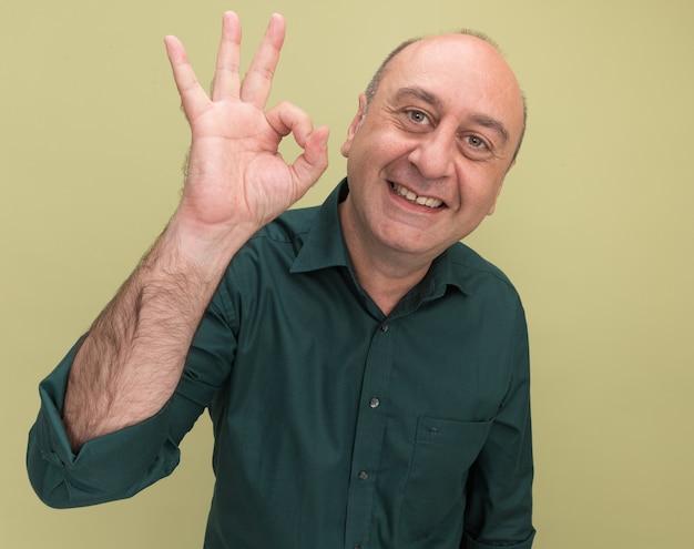 Uśmiechnięty mężczyzna w średnim wieku na sobie zieloną koszulkę pokazując dobry gest na białym tle na oliwkowej ścianie