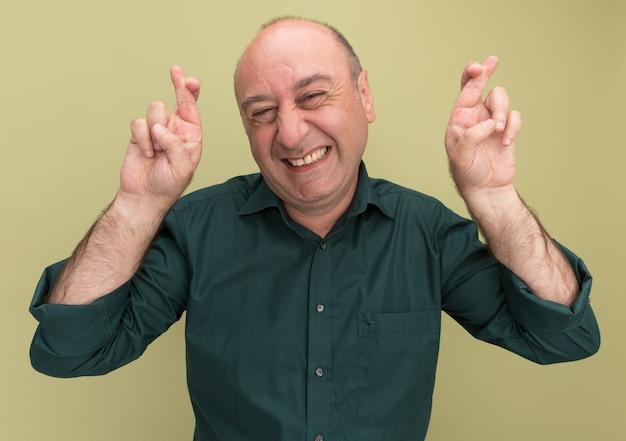 Uśmiechnięty mężczyzna w średnim wieku na sobie zieloną koszulkę skrzyżowanymi palcami na oliwkowej ścianie
