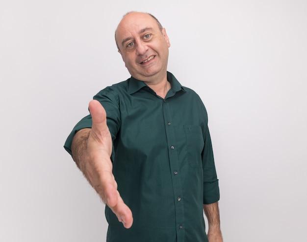 Uśmiechnięty mężczyzna w średnim wieku na sobie zieloną koszulkę wyciągając rękę na aparat na białym tle na białej ścianie z miejsca na kopię