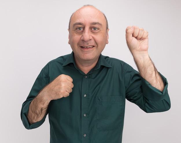 Uśmiechnięty mężczyzna w średnim wieku na sobie zielony t-shirt stojący w pozie walki na białym tle na białej ścianie