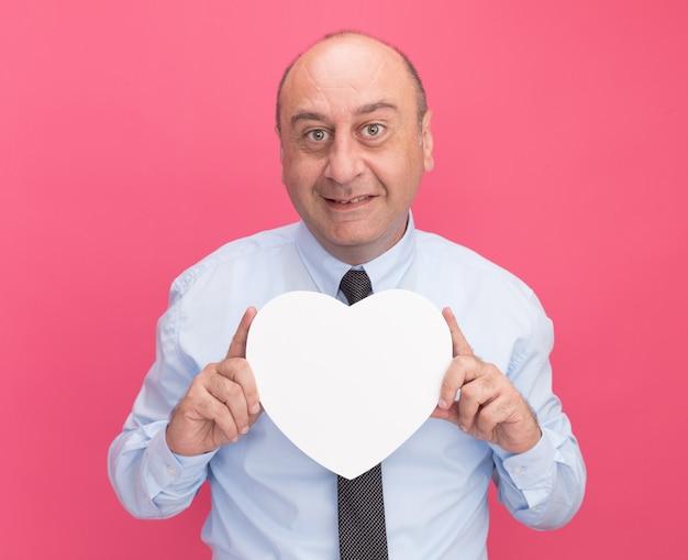 Uśmiechnięty mężczyzna w średnim wieku ubrany w białą koszulkę z krawatem trzyma pudełko w kształcie serca na białym tle na różowej ścianie